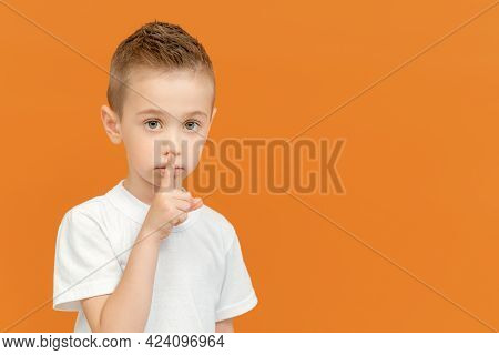 Young Beautiful Blonde Caucasian Kid Put Forefinger To Lips As Sign Of Silence, Isolated On Yellow B