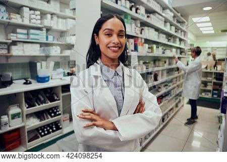Portrait Of Young African American Pharmacist Standing Between Aisle In Chemist With Colleague Worki