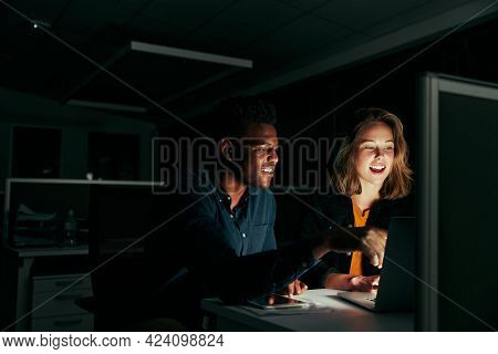 Happy Businessman And Businesswoman Working On Laptop Overtime In Night Time