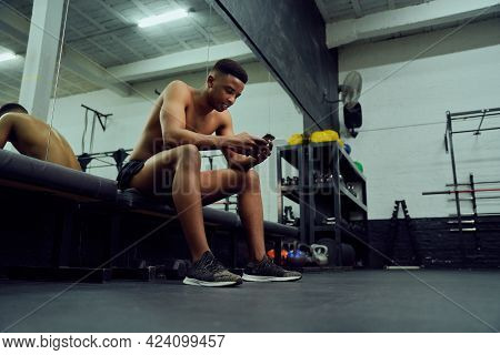 Young African American Male Looking At His Phone To Reply To An Online Message. Mixed Race, Male Per