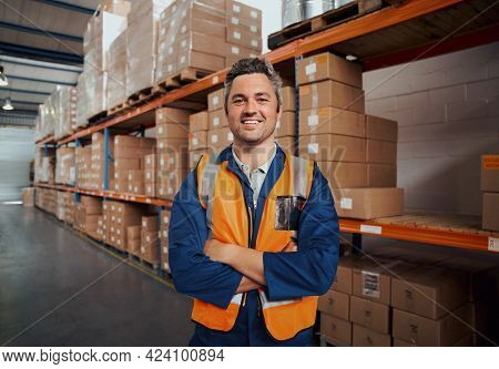Cheerful Man Standing At Manufacturing Industry Looking At Camera With His Arm Crossed