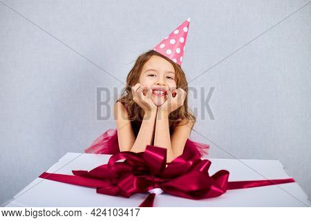 Portrait Of Joyful Little Girl In Pink Dress And Hat Put Her Elbows On Big Present Gift Box
