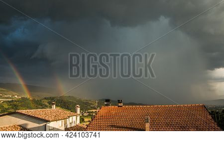 View Of Dark Storm Cloud Over Foligno With Double Rainbow In Umbria