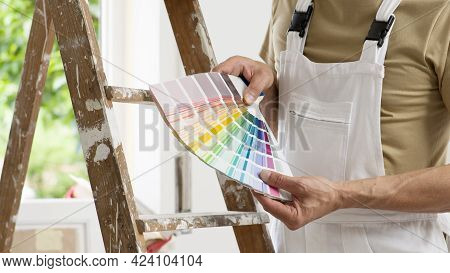 Hands Of House Painter Man Decorator Choose The Color Using The Sample Swatch, Work Of The House To