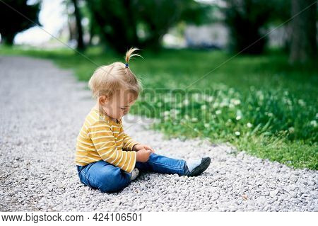 Little Girl With A Ponytail On Her Head Sits On A Gravel Path In A Green Park