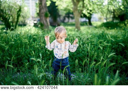 Kid Stands With His Hands Up Among The Tall Green Grass In The Park