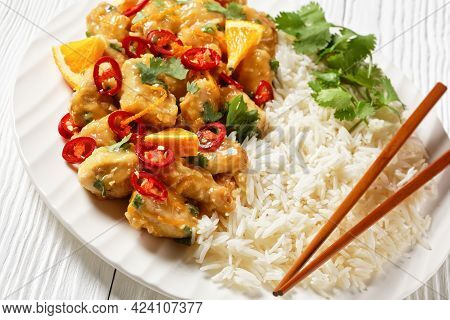 Mango Glazed Spicy Chicken Breast Chunks With Rice On A White Plate With Chopsticks, On A  Wooden Ta
