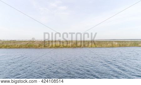 Side Aerial View Of A Wide Calm River With Ripples With Green Grass Shore And Blue Cloudy Sky On The