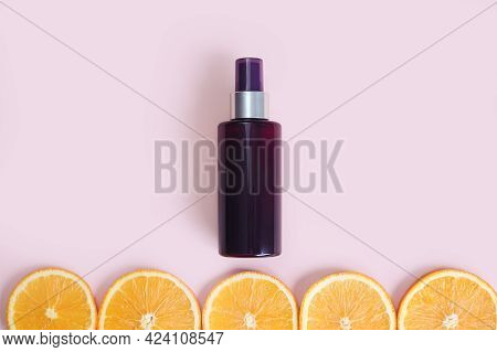 Unbranded Dark Brown Spray Bottle And Line Of Orange Slice Circles On Pink Background. Cosmetic Pack