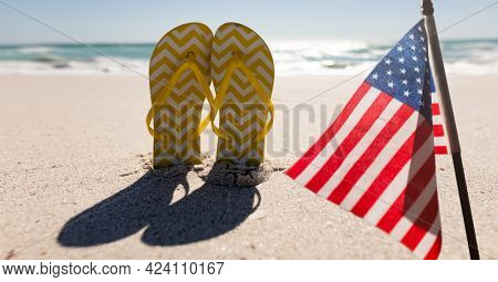 Composition of american flag and flip flops on beach. united states of america celebration, holiday, patriotism and independence concept digitally generated image.
