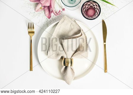 Elegant table setting with floral decor, flat lay. Wedding or festive table setting. Plate and cutlery with pink flowers on white background