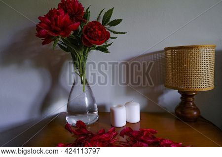 Red Peonies In Glass Vase, Straw Lamp, White Candles On Wooden Commode Across White Wall. Interior D