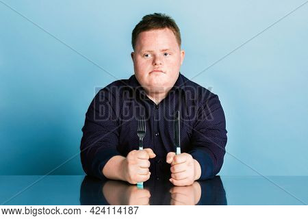 Hungry kid with down syndrome waiting for dinner