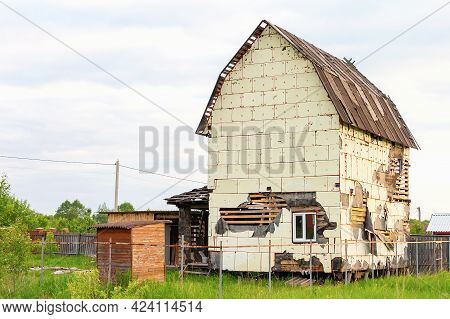 Destroyed And Damaged House On Farm Or Ranch With Partially Collapsed Walls And Holes In It After St