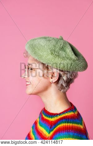 Side view of a cute girl wearing a rainbow sweater and a green beret in a pink background