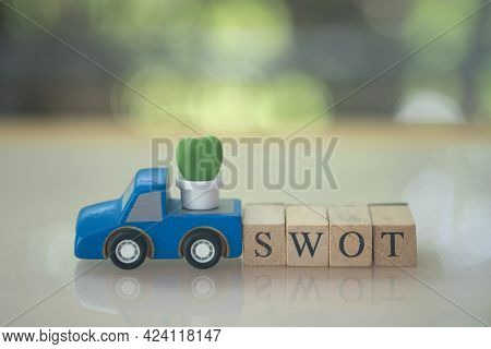 Miniature Cactus Placed On Truck Wood Toy Car With Wood Block Of Swot. Swot Acronym Of Strength, Wea