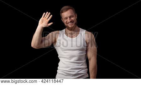 The Man Laughs And Waves His Hand At The Camera. Happy Man Glad To Meet You. Muscular Athlete In A W