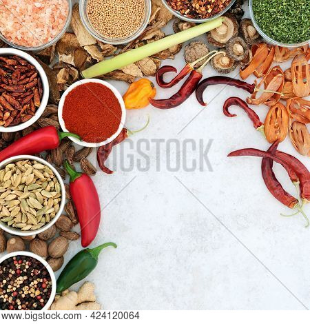 Healthy culinary spice and herb border with fresh and dried herbs and spices on mottled grey background with copy space. Health food concept. Top view, flat lay.