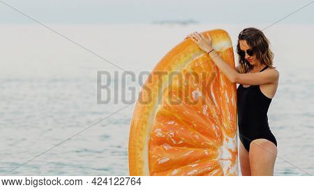 Girl in a black swimsuit with an orange inflatable float at the beach