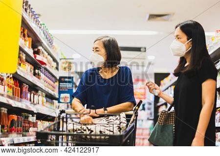 Senior Woman And Daughter In Medical Mask Doing Shopping In Supermarket