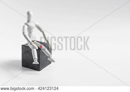 A Figure Of A Wooden Man Sitting On A Dark Podium. The Figure Of A Wooden Man With A Red Knee On A L