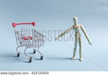 The Figure Of A Wooden Man Pointing At An Empty Metal Basket. Figure Of A Wooden Man On A Light Back