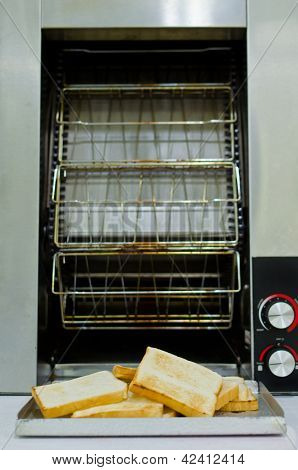 Metallic Toaster And  Hot Toasts Ready To Serve For The Breakfast.