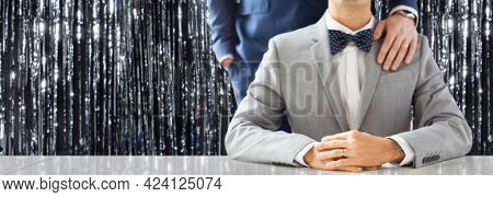 lgbt, homosexuality and same-sex marriage concept - close up of male gay couple with wedding rings over foil fringe curtain on background