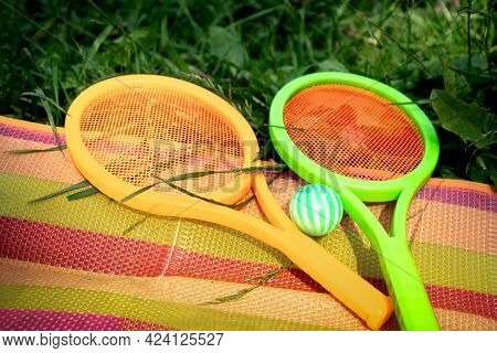 Toy Tennis Rackets With Ball Lying On Colorful Striped Blanket Spread Out On The Grass. Active Outdo
