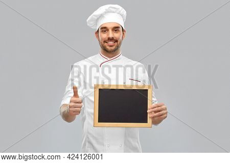 cooking, culinary and people concept - happy smiling male chef in toque showing chalkboard and thumbs up over grey background