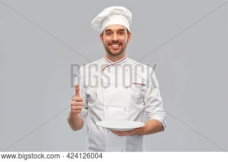 cooking, culinary and people concept - happy smiling male chef in toque holding empty plate and showing thumbs up over grey background