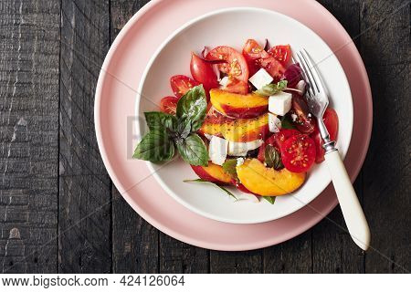 Salad With Tomatoes, Peach, Red Onion, Cheese And Basil. Top View.