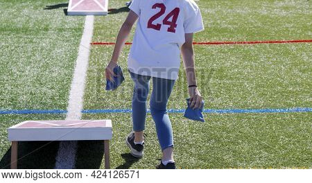 Rear View Of A Persong Throwing A Bean Bag While Playing Cornhole On A Green Turf Field.