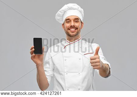 cooking, culinary and people concept - happy smiling male chef in toque showing smartphone and thumbs up over grey background