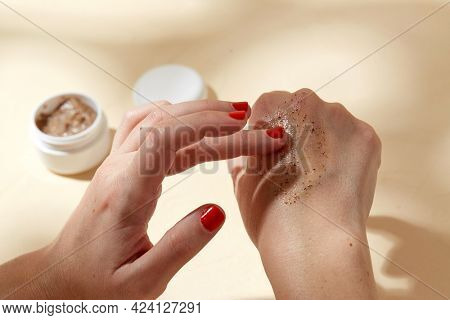 beauty, cosmetics and object concept - close up of hands applying natural body scrub to skin on beige background