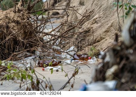 People And Ecology. Riverside Pollution. Trash And Plastics At The Beach. Human Pollution Of Nature.