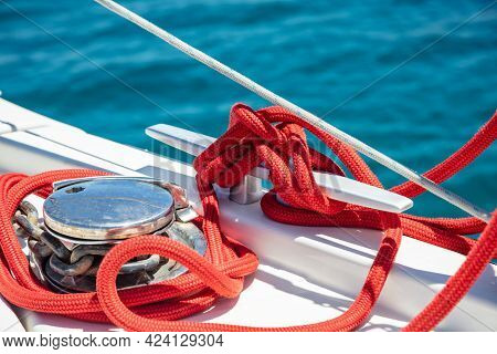 Sailing Boat Mooring Rope Tied On Cleat. Heavy Metal Chain Around The Winch