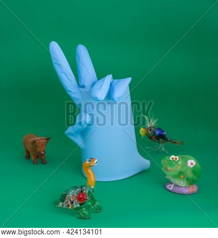 One Blue Medical Glove With Bent Fingers On Isolated Background With Smiling Toy Frog, Turtle, Bird,