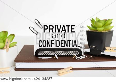 Private And Confidential. Business Card Holder On A Work Table, On A Notebook, Near A Flowerpot