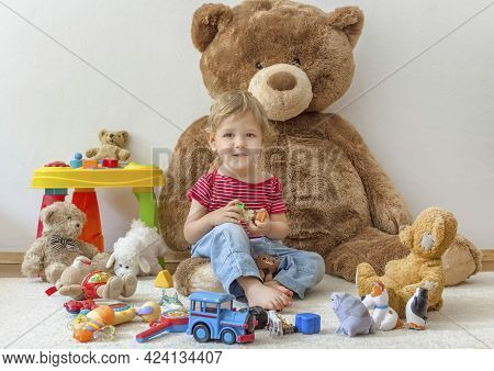 Sweet Happy Child Boy Having Fun Playing With His Giant Teddy Bear And Many Colorful Toys, Indoor At
