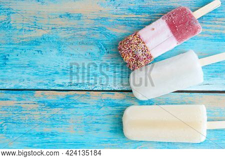 Frozen Assorted Ice Lollies On A Wooden Background
