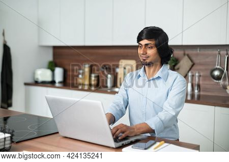 Smiling Optimistic Young Indian Man Wearing Casual Shirt Using Laptop Sitting In The Kitchen At Home