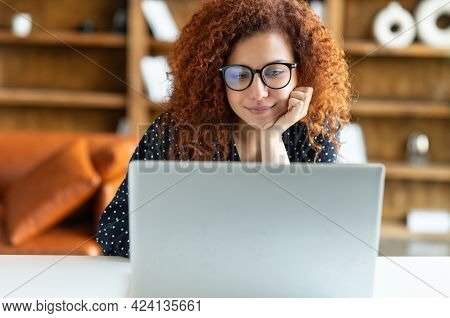 Portrait Of Positive Red-haired Curly Pretty Female Freelancer Businesswoman Sitting At The Desk And