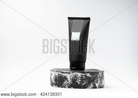 Unbranded Black Tube Of Cosmetic Product On Black And White Pedestal Or Podium On White Background.