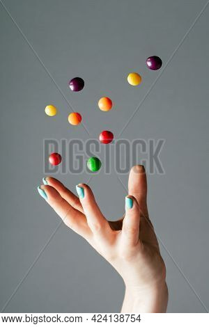 Female Hand Throwing Bright Multi-colored Round Candies Into Air. Levitating Candy. Copy Space. Vert