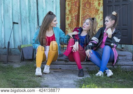 Girls In The Style Of The Nineties. Country Girls Sit On A Wooden Porch.