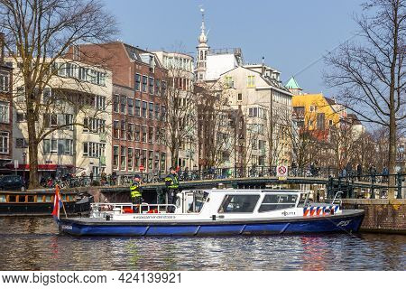 Amsterdam, Netherlands - 12 March 2016: Dutch Police Patrol On A Barge. Typical Dutch Houses. City V