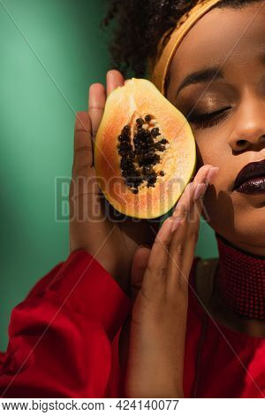 Partial View Of Young African American Woman With Closed Eyes Holding Half Cut Of Ripe Papaya Near F
