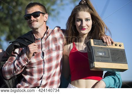 Man And Woman Dressed In The Style Of The Nineties With A Cassette Tape Recorder.