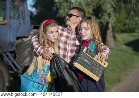 Funny Man With Cassette Recorder Hugs Girls. People In The Style Of The Nineties.